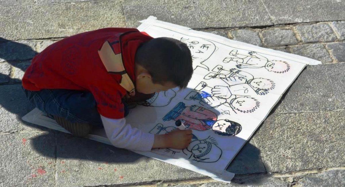 Estudiante de primaria dibujando en la Feria realizada en la Plaza San Francisco de La Paz